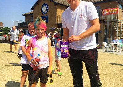 1st XI Captain Nathan Armstrong presenting the winner of the U10s colour run race with their prize
