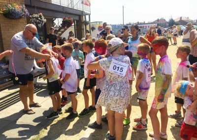 Cricket Coach Richard Dearden presenting runners medals at the 2018 Colour Run