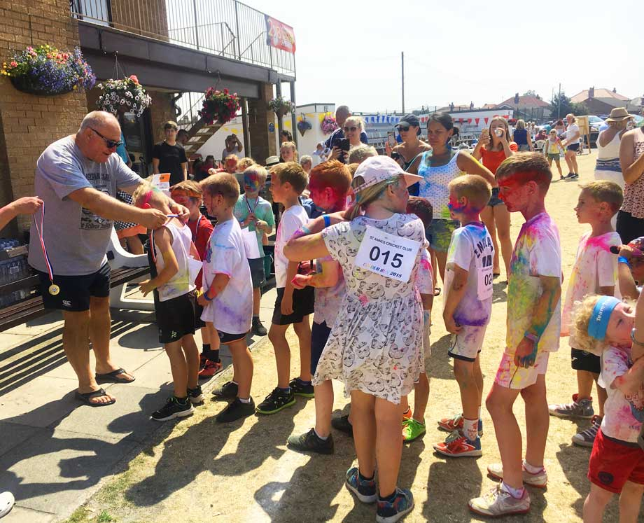 Cricket Coach Richard Dearden presenting runners medals at the 2018 Colour Run